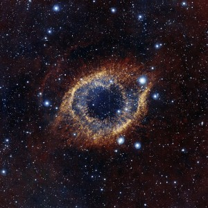 "Image: ""ESO's Visible and Infrared Survey Telescope for Astronomy (VISTA) has captured this unusual view of the Helix Nebula (NGC 7293), a planetary nebula located 700 light-years away. The coloured picture was created from images taken through Y, J and K infrared filters. While bringing to light a rich background of stars and galaxies, the telescope's infrared vision also reveals strands of cold nebular gas that are mostly obscured in visible images of the Helix."" Wikimedia Commons (CC BY 3.0)  https://creativecommons.org/licenses/by/3.0/deed.en"
